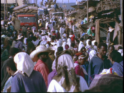 A market in Africa swarms with crowds of shoppers and... Stock Video Footage