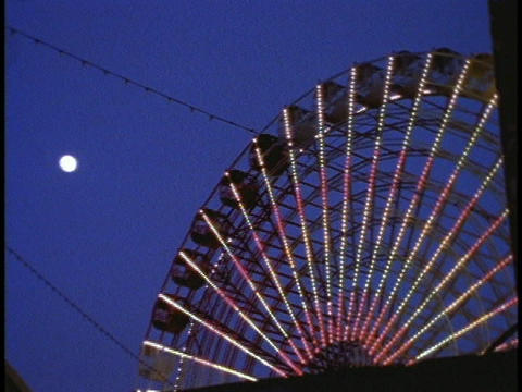 A ferries wheel turns in an amusement park Footage