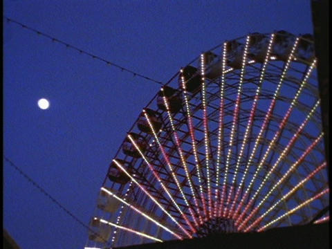 A ferries wheel turns in an amusement park Stock Video Footage