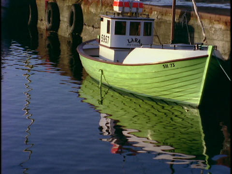 A fishing boat floats near a dock Stock Video Footage