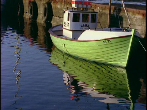 A fishing boat floats near a dock Footage