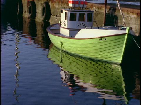 A fishing boat floats near a dock Stock Video Footage
