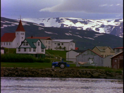 A tractor drives by a lake in a fishing village in Iceland Stock Video Footage