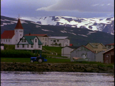 A tractor drives by a lake in a fishing village in Iceland Footage
