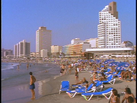 Crowds relax on a beach in Tel Aviv, Israel Stock Video Footage