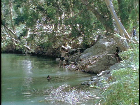 A child swings on a rope into the River Jordan Stock Video Footage