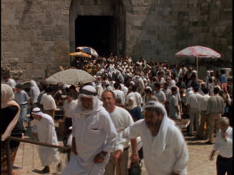 Palestinians exit the Damascus Gate in Jerusalem Stock Video Footage