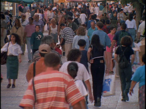 Crowds of pedestrians walk on a street in Israel Stock Video Footage