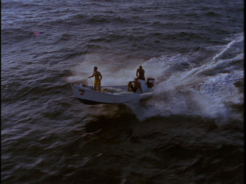 A small motorboat speeds across the water Footage