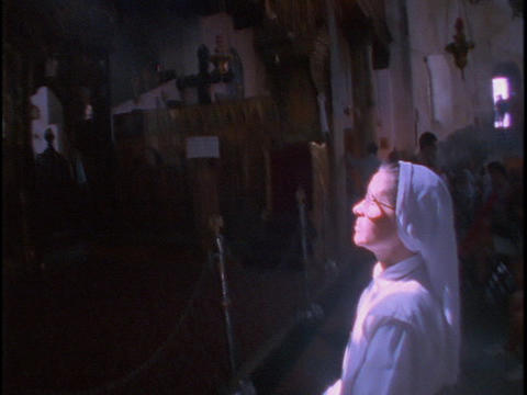A Catholic nun stands in a pool of light coming from the... Stock Video Footage