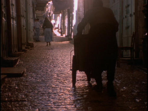 A man wheels a hand cart through old city of Jerusalem Stock Video Footage