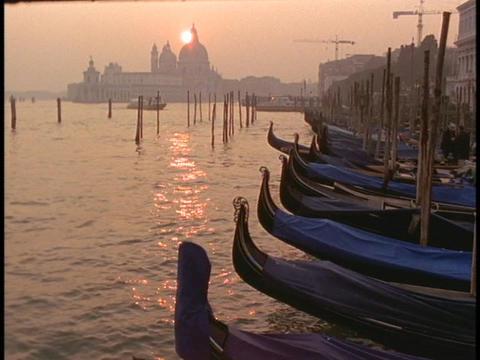 Gondolas lie moored in a Venice harbor Stock Video Footage