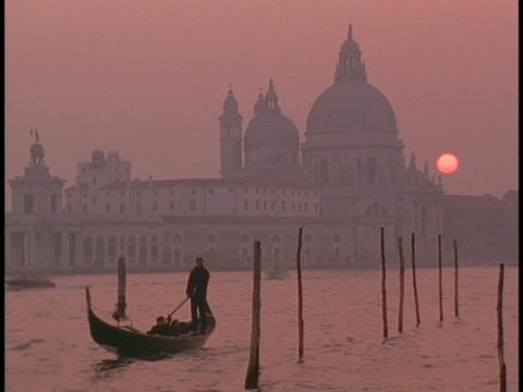 A gondola in Venice sails away from a cathedral Live Action