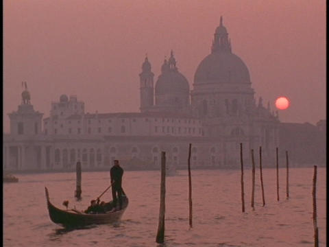 A gondola in Venice sails away from a cathedral Stock Video Footage