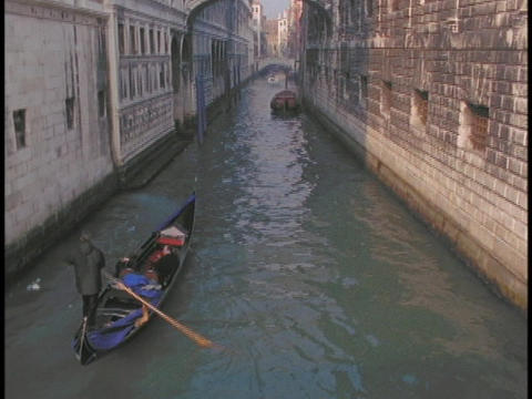 A gondola sails through a narrow canal in Venice, Italy Footage