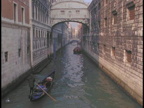 A gondola sails through a narrow canal in Venice, Italy Stock Video Footage