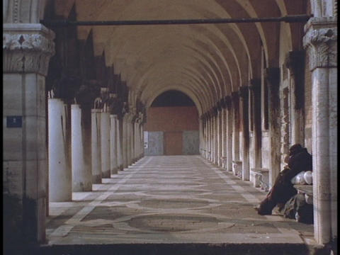 An individual sits under columns in a Roman building Stock Video Footage