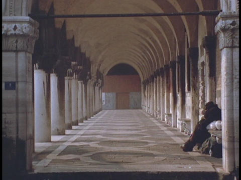 An individual sits under columns in a Roman building Footage