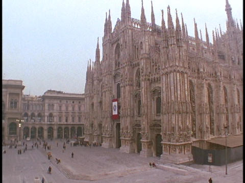 Pedestrians walk near the Duomo Cathedral in Milan, Italy Stock Video Footage