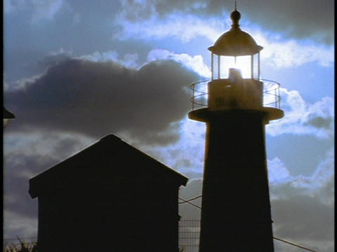 The sun shines brightly through a lighthouse beacon Stock Video Footage