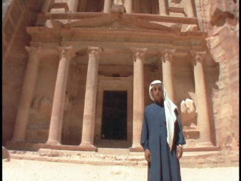 An Arab man in traditional clothing stands in front of the ruins at Petra, Jordan Footage