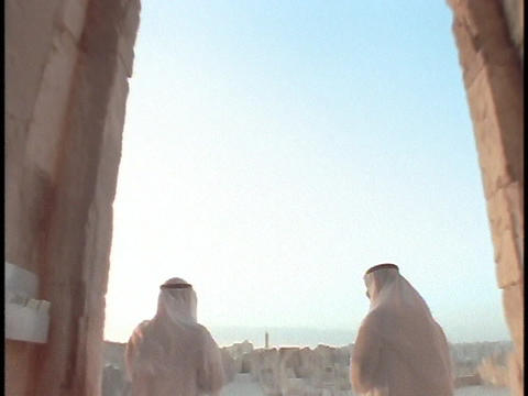 Saudi Arabian businessmen stand in front of an ancient ruin Footage