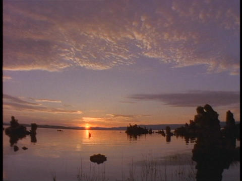 The sun sets on the horizon behind Lake Mono in California Stock Video Footage