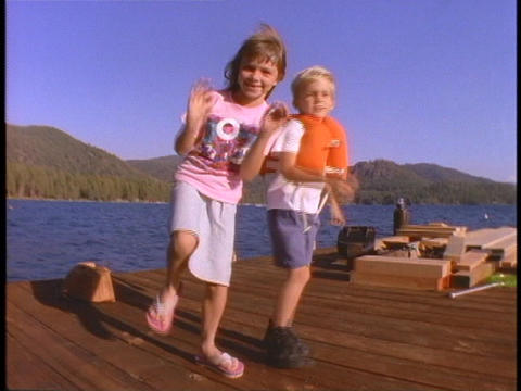 children perform a silly dance on a dock Stock Video Footage