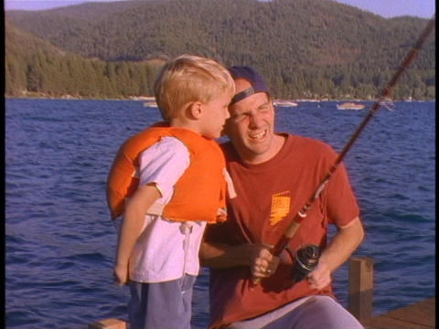A father teaches his son to fish Stock Video Footage