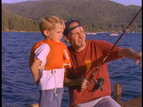 A father teaches his son to fish Footage