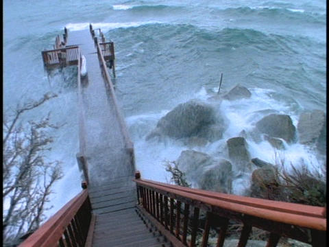 Waves crash over a pier during a storm Footage