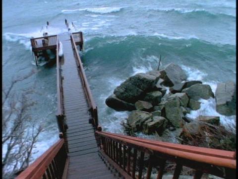 Waves crash over a pier during a storm Stock Video Footage