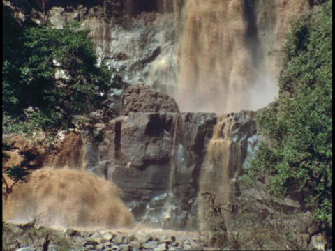 Muddy waterfalls flow over cliffs Stock Video Footage