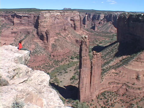 A woman sits on the edge of a cliff at Canyon de Chelly... Stock Video Footage