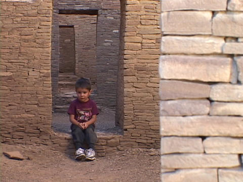 An American Navajo boy sits in a doorway of a pueblo in... Stock Video Footage