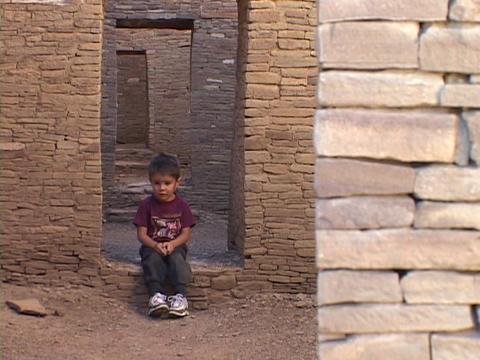 An American Navajo boy sits in a doorway of a pueblo in... Stock Video Footage