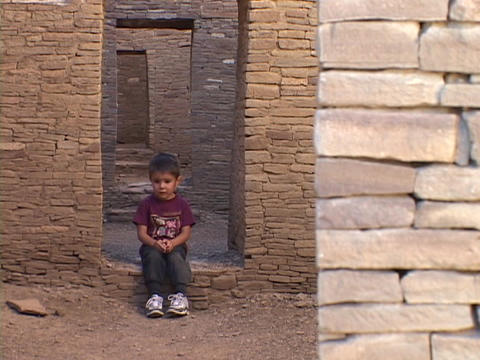 An American Navajo boy sits in a doorway of a pueblo in Chaco Canyon, Arizona Footage