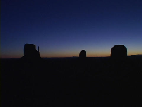 Monument Valley in silhouette stands against a deep, blue sky Footage