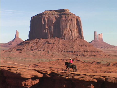 A cowboy on horseback rides through in Monument Valley, Utah Stock Video Footage