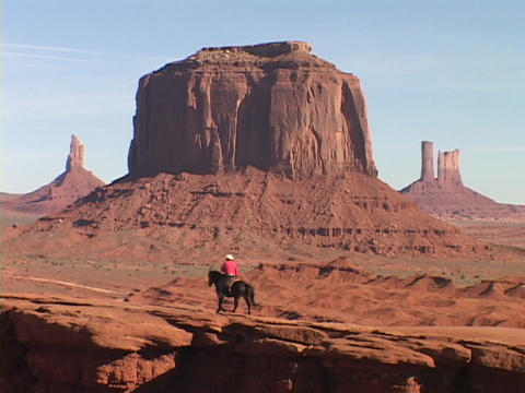 A cowboy on horseback rides through in Monument Valley, Utah Footage