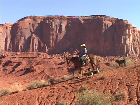 A cowboy on horseback rides down the trail in Monument... Stock Video Footage