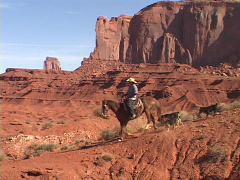 A cowboy on horseback rides down the trail in Monument Valley, Utah Footage