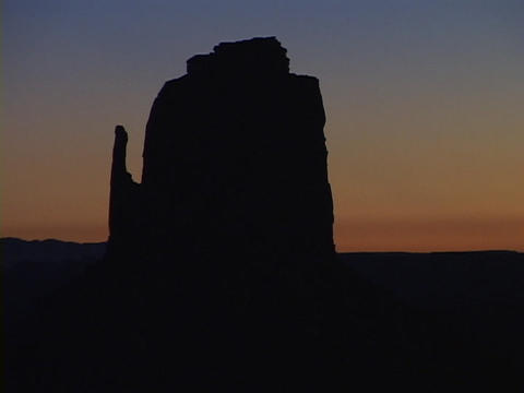 Golden light silhouettes a rock formation in Monument Valley, Utah Footage
