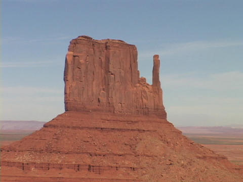 The East Mitten Butte stands against a blue sky in Monument Valley, Utah Footage
