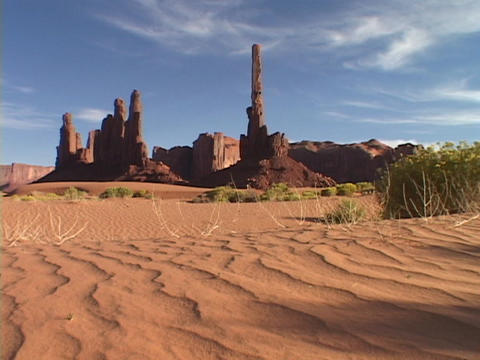 Sand patterns spread at the base of the Totem Pole rock formation in Monument Valley, Utah Footage