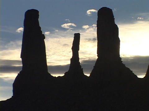 The Three Sisters stand in silhouette in Monument Valley, Utah Footage