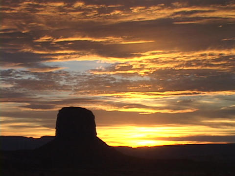 A butte stands in silhouette beneath golden clouds in Monument Valley Footage