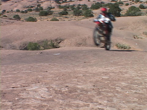 Off road motorcycles drives across the Moab desert Stock Video Footage