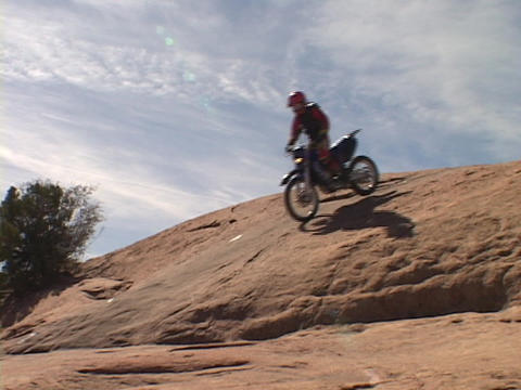 A dirt bike ride performs a stunt down a hill in Moab Footage