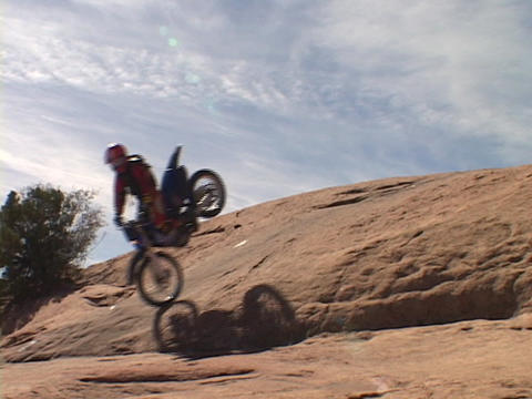 A dirt bike ride performs a stunt down a hill in Moab Stock Video Footage